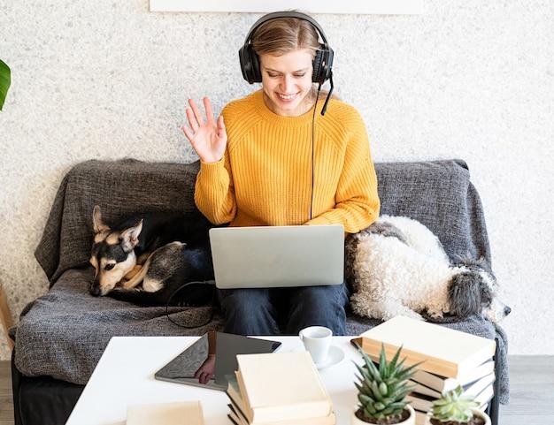 Ensino à distância. e-learning. jovem mulher sorridente com suéter amarelo e fones de ouvido pretos, estudando on-line usando um laptop, sentada no sofá em casa