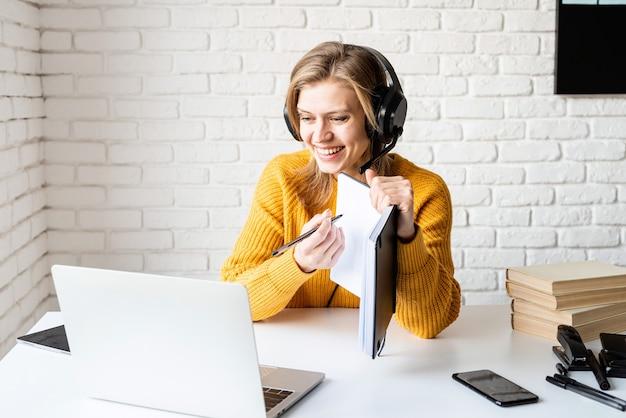 Ensino à distância. e-learning. mulher jovem com fones de ouvido pretos estudando on-line usando um laptop