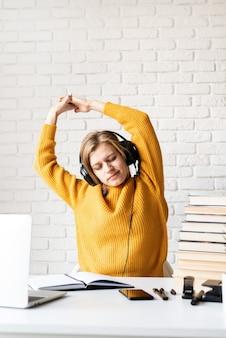 Ensino à distância. e-learning. mulher jovem com fones de ouvido pretos sentada na mesa se espreguiçando após um longo estudo