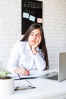 Ensino à distância. e-learning. mulher morena triste ou deprimida dormindo no local de trabalho