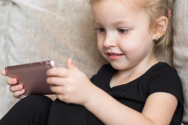 Ensino a distância, educação on-line para crianças. garota feliz, segurando o smartphone nas mãos. criança assistindo desenhos animados on-line, crianças dependência de computador, controle dos pais.