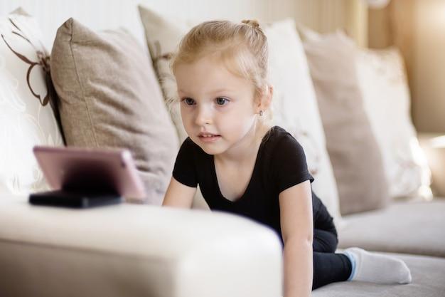 Ensino a distância, educação on-line para crianças. menina estudando em casa na frente do smartphone. criança assistindo desenhos animados on-line, crianças dependência de computador, controle dos pais.