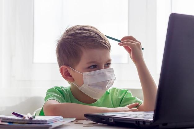 Ensino a distância, educação online. distância social, auto-isolamento durante a quarentena. pré-escolar ou estudante em máscara médica estudando em casa com o laptop, fazendo lição de casa para a escola de desenvolvimento