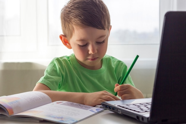 Ensino a distância, educação online. distância social e auto-isolamento durante a quarentena. pré-escolar ou estudante estudando em casa com o notebook e fazendo lição de casa para a escola de desenvolvimento.