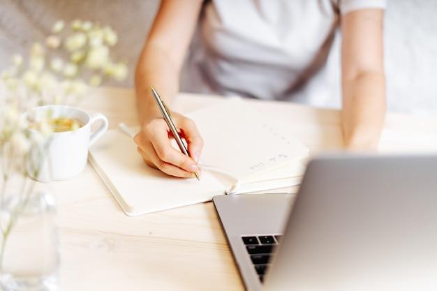 Ensino à distância, educação online e trabalho. mulher de negócios escreve metas, planos, tarefas e lista de desejos no caderno na mesa, trabalhando em casa. usando laptop.