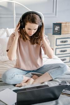 Ensino à distância, educação online e trabalho. mulher feliz casual com os fones de ouvido trabalhando em um laptop remotamente de casa na cama.
