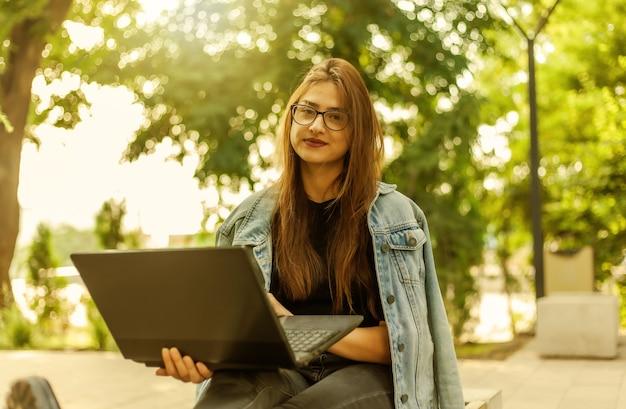 Ensino à distância. jovem estudante com uma jaqueta jeans e óculos olha para a câmera com um aptop na mão enquanto está sentada no banco do parque