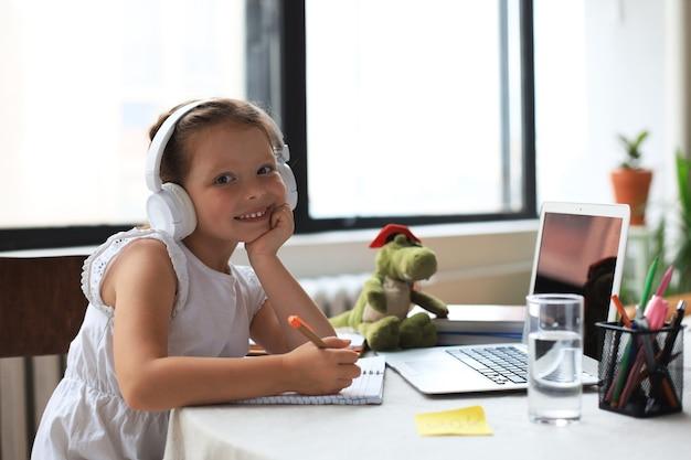 Ensino à distância. menina alegre em fones de ouvido usando laptop, estudando através do sistema de e-learning online.