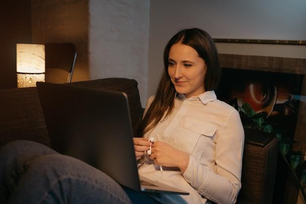 Ensino à distância. uma mulher caucasiana com fones de ouvido, estudando remotamente em seu laptop. uma garota feliz, deitado com um notebook de alumínio no sofá. educação em casa.