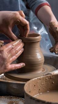 Ensino de cerâmica para crianças. o professor dá uma aula magistral em modelagem