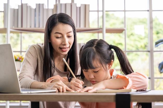 Ensino doméstico aprendendo em casa durante a pandemia de vírus. mulher asiática com a filha na sala de estar, usando máscaras cirúrgicas para protegê-los do vírus.