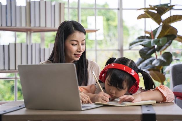 Ensino doméstico, aprendizagem em casa durante a pandemia de vírus, mulher asiática com sua filha