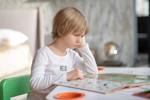 Ensino doméstico durante a pandemia. um menino entediado lendo um livro em casa