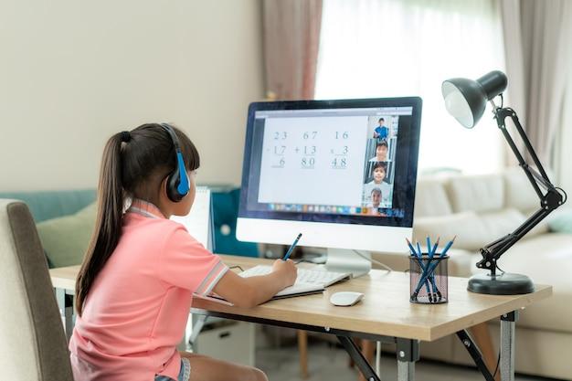 Ensino eletrónico asiático da videoconferência da estudante com professor e colegas no computador na sala de visitas em casa.