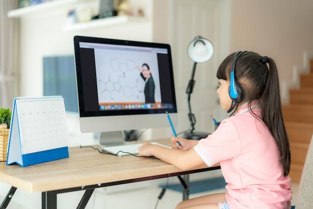 Ensino eletrónico asiático da videoconferência da estudante com professor no computador na sala de visitas em casa.