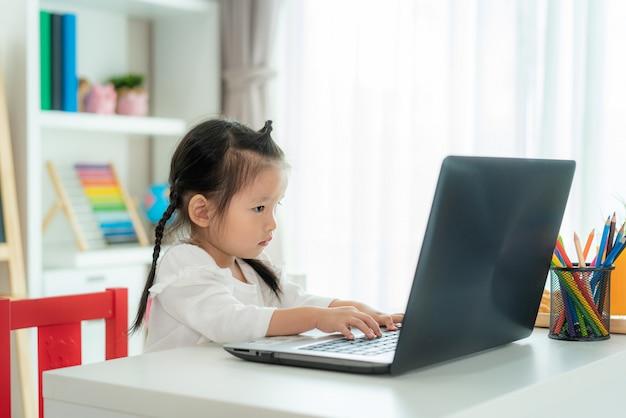 Ensino eletrónico asiático da videoconferência da menina da escola do jardim de infância com o professor no portátil na sala de visitas em casa. ensino em casa e ensino à distância, online, educação protegem do vírus covid-19.