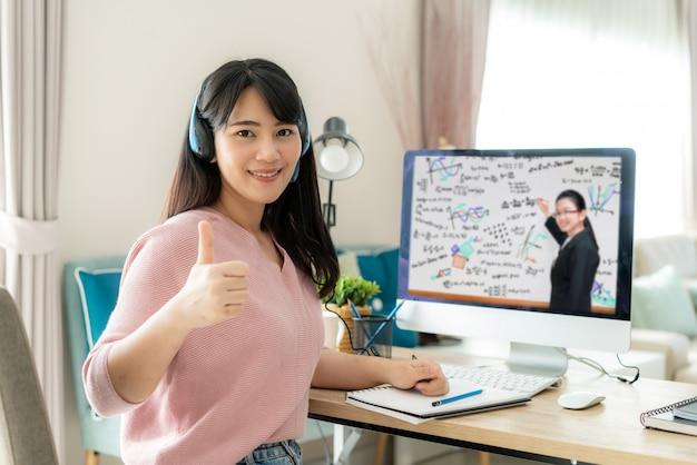 Ensino eletrónico asiático da videoconferência do estudante de mulher com professor no computador e polegar acima na sala de visitas em casa.
