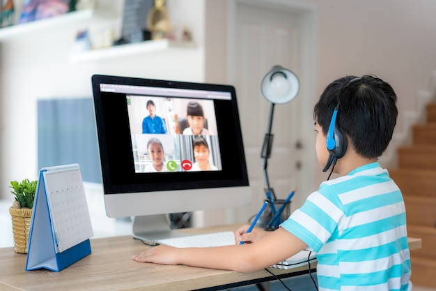 Ensino eletrónico asiático da videoconferência do estudante do menino com professor e colegas no computador na sala de visitas em casa. ensino em casa e ensino à distância, online, educação e internet.