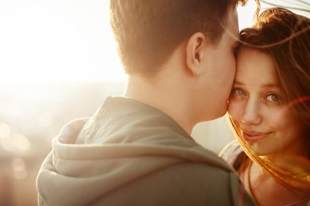 Ensolarado retrato ao ar livre do jovem casal feliz