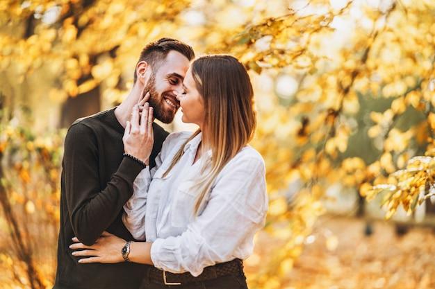 Ensolarado retrato de um jovem casal apaixonado andando no parque outono.