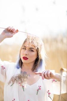 Ensolarado retrato de uma linda jovem no fundo de um campo de trigo