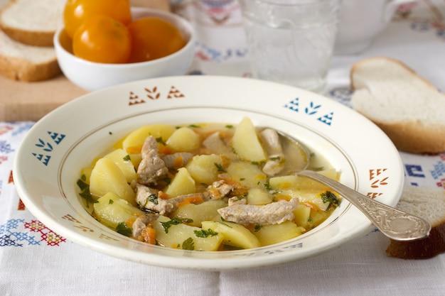 Ensopado, assado ou sopa com carne e batatas, servido com tomate enlatado e pão.