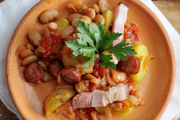 Ensopado com batatas, feijão, defumado em uma panela de barro
