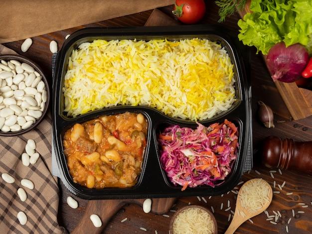 Ensopado de carne com batata e castanhas em molho de tomate com guarnição de arroz e salada de cenoura de repolho para viagem