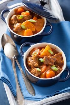 Ensopado de carne com batata e cenoura em uns potenciômetros azuis