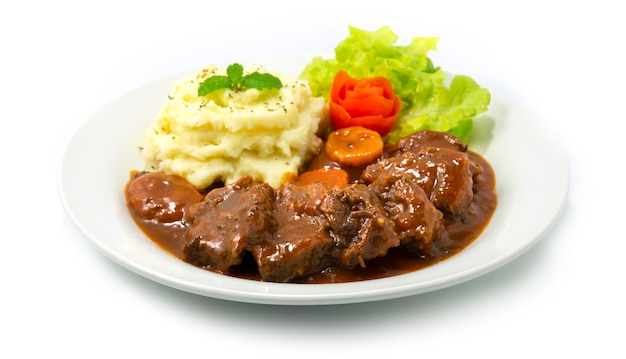 Ensopado de carne com molho de vinho tinto servido purê de batata delicioso prato principal comida europeia decoração estilo vegetais esculpidos vista lateral
