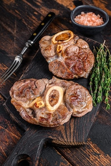 Ensopado de carne com osso pernil de bovino osso buco, bife italiano ossobuco. fundo de madeira escuro. vista do topo.