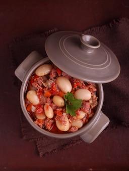 Ensopado de feijão com carne e legumes em um fundo escuro de madeira