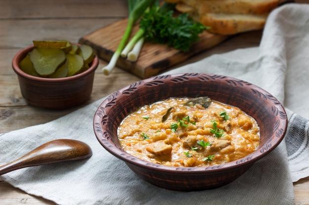 Ensopado de feijão e carne, servido com picles, pão e alho. estilo rústico.
