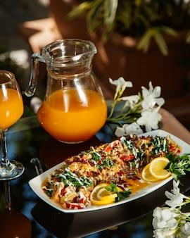 Ensopado de legumes decorado com ervas e limão, servido com suco de laranja