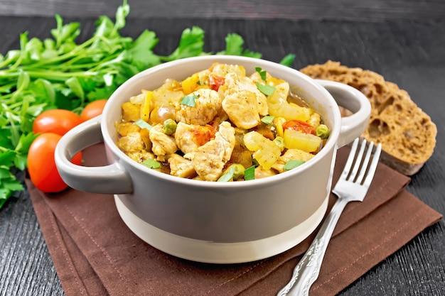 Ensopado de peito de frango, tomate, talo de aipo, cenoura, ervilha e cebola em uma terrina em um guardanapo contra uma placa de madeira escura
