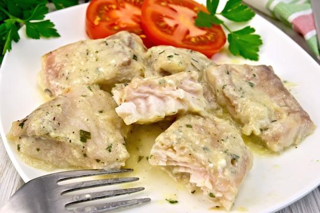 Ensopado de peixe em molho cremoso, tomate, salsa no prato, garfo, guardanapo em tábuas de madeira de luz de fundo
