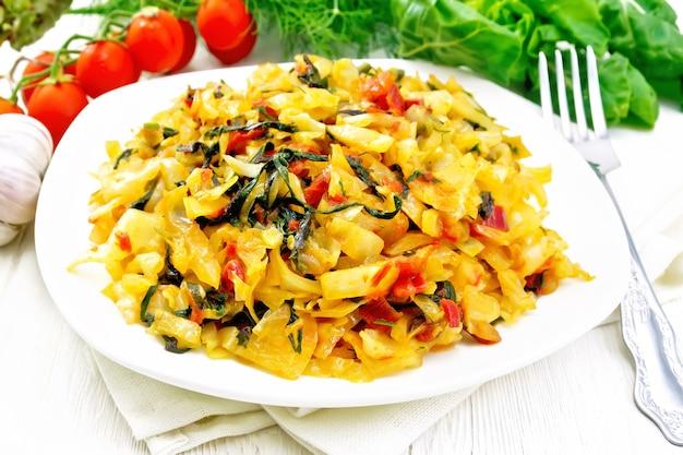 Ensopado de repolho com folhas de beterraba e tomate em um prato branco no guardanapo, salsa, alho e um garfo no fundo da placa de madeira leve