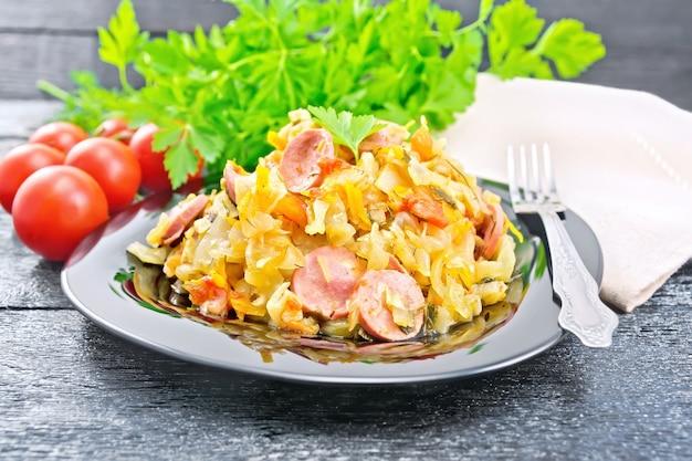 Ensopado de repolho com salsichas em um prato preto, guardanapo, tomate, salsa e garfo em uma placa de madeira