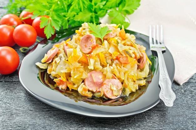 Ensopado de repolho com salsichas em um prato preto, toalha, tomate, salsa e garfo em um fundo escuro de tábua de madeira