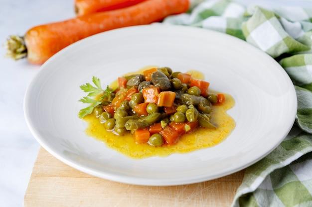 Ensopado de vegetais frescos e saudáveis com cenouras em um prato sobre uma tábua de madeira