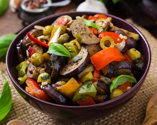 Ensopado picante quente de berinjela, pimentão, azeitonas e alcaparras com folhas de manjericão.