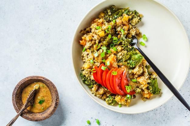 Ensopado vegetariano com grão de bico, batata doce e tomate fresco em um prato branco.