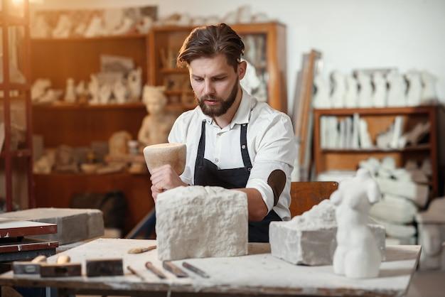 Entalhador de pedra trabalha com martelo de madeira e formão em calcário.