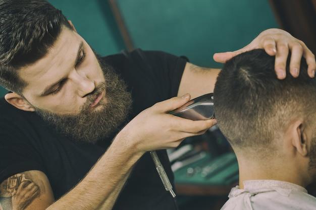 Então, no trabalho. retrato de um barbeiro barbudo, dando um corte de cabelo para seu cliente atentamente