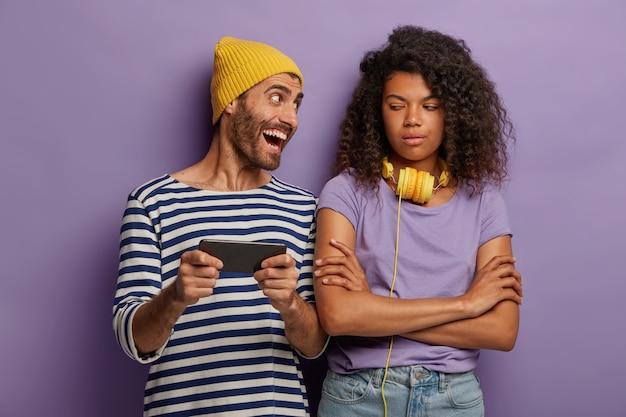 Entediada insatisfeita adolescente afro-americana mantém as mãos cruzadas, olha como o amigo joga videogame no smartphone moderno, obcecado com o novo aplicativo.