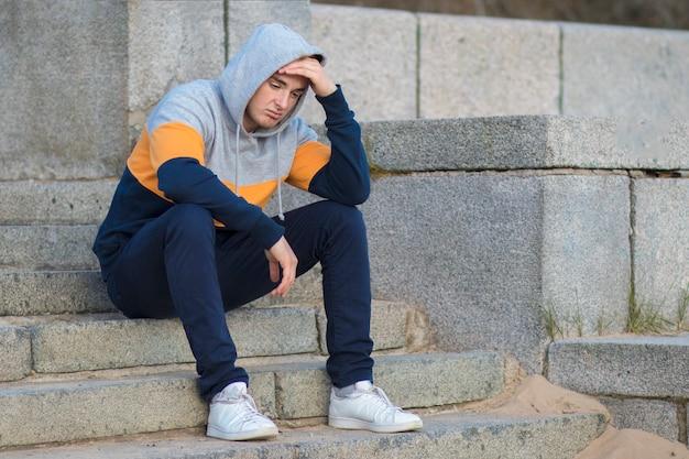 Entediado bonitão solitário sentado na escada e segurando sua cabeça com a mão. frustrado e triste homem chateado.