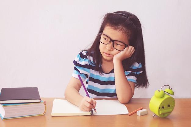 Entediado e cansado menina asiática estudante fazendo lição de casa