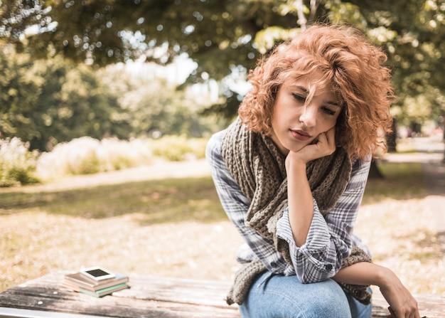 Entediado feminino sentado no banco com livros e telefone no parque