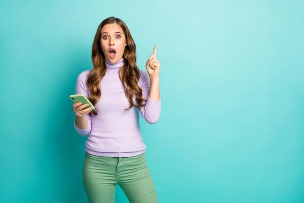 Entendi! foto de uma linda senhora chocada, segurando as mãos do telefone, ter uma ideia de pós-criação criativa, levantar o dedo, pessoa inteligente usar pulôver roxo, calça verde pastel