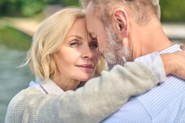 Entendimento. mulher bonita loira de meia idade com olhar feliz abraçando um homem barbudo com os olhos fechados, em pé no ar fresco em um dia ensolarado
